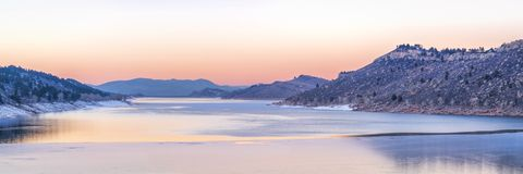 Calm winter dusk over mountain lake. Panoramic view of a calm winter dusk over partially frozen Horsetooth Reservoir near Fort Collins in northern Colorado Royalty Free Stock Images