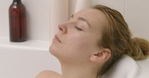 Calm woman in bath. Calm woman relaxing in bath. She is lying in bathtub and resting stock video