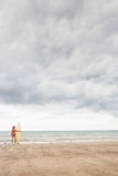 Calm woman in bikini with surfboard on beach Royalty Free Stock Photography