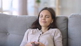 Calm woman in earphones chilling listening to music using app stock footage