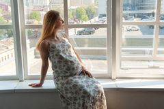Calm woman in expectancy for a child relaxing at home. Waiting for a birth of new life concept. Beautiful tender pregnant girl sitting on window sill and looking stock image