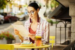 Calm woman looking through the menu while being in a cafe royalty free stock photography