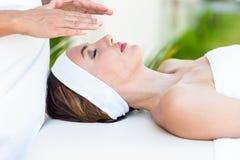 Calm woman receiving reiki treatment Royalty Free Stock Photos