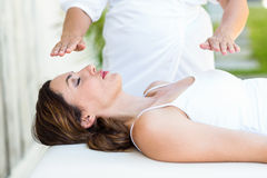 Calm woman receiving reiki treatment. In the health spa Stock Image