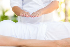 Calm woman receiving reiki treatment. In the health spa stock photos