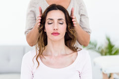 Calm woman receiving reiki treatment. Calm women receiving reiki treatment on white background Stock Image