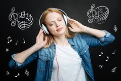 Calm woman relaxing while listening to music with her eyes closed. Peaceful music. Relaxed young woman standing with her eyes closed and feeling good while stock photos