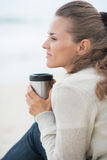 Calm woman sitting on beach with cup of beverage Royalty Free Stock Photography