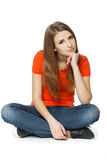 Calm woman sitting on the floor. With chin on hand, over white background Stock Photo