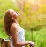Calm woman on terrace. Closeup on beautiful calm woman enjoying nature on terrace in luxury cottage, spa resort, zen balance, summer vacation, harmony conception Stock Image