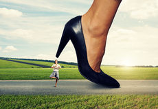 Calm woman under big female heel Royalty Free Stock Photos