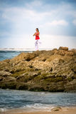 Calm woman in zen moment in meditating on rock in sea Royalty Free Stock Image