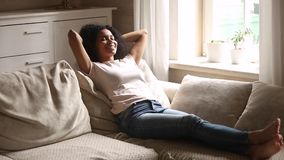 Calm african woman rest on couch enjoy stress free day. Calm young african woman rest lying on comfortable couch enjoy nap, lazy healthy smiling black girl stock video