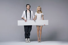 Calm young couple holding empty board Stock Photo