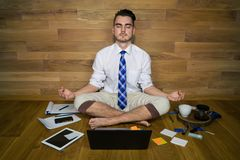 Calm young man in funny clothes sits on the floor against a wall after work. With laptop and other gadgets. Barefoot businessman works at home and tries to find Royalty Free Stock Image