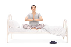 Calm young man meditating seated on a bed Stock Image