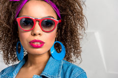 Calm young woman with accessory. Portrait of serene african female expressing her desire. She is wearing bright sunglasses and big earrings. Copy space Stock Image