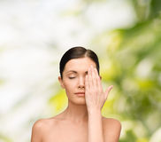 Calm young woman covering face with hand Stock Images
