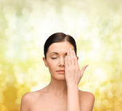 Calm young woman covering face with hand Royalty Free Stock Image