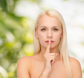 Calm young woman with finger on lips Royalty Free Stock Images