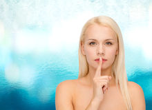 Calm young woman with finger on lips Royalty Free Stock Photo