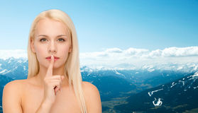 Calm young woman with finger on lips Stock Photography