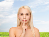 Calm young woman with finger on lips Royalty Free Stock Image