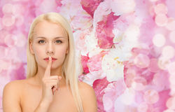 Calm young woman with finger on lips Stock Photo