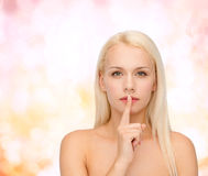 Calm young woman with finger on lips Stock Images