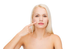 Calm young woman pointing at her cheek Royalty Free Stock Photos