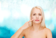 Calm young woman pointing at her cheek Royalty Free Stock Photography