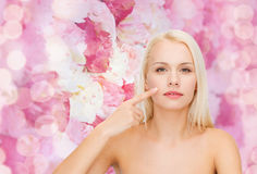 Calm young woman pointing at her cheek Stock Photos