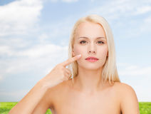 Calm young woman pointing at her cheek Stock Image