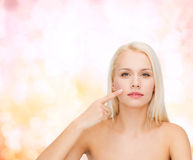 Calm young woman pointing at her cheek Royalty Free Stock Image