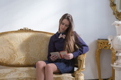 Calm young woman reading on sofa Stock Photography