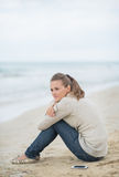 Calm young woman sitting on cold beach Stock Image