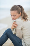 Calm young woman sitting on cold beach Stock Photo