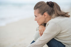 Calm young woman sitting on cold beach Royalty Free Stock Image