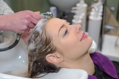 Calm young woman sitting at hairdressers Stock Photo
