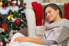 Calm young woman sitting near Christmas tree Stock Photography