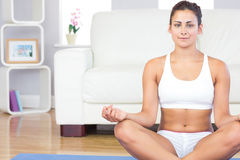 Calm young woman in sportswear sitting in lotus position on her exercise mat Stock Images