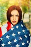 Calm young woman warp in US american flag Stock Images