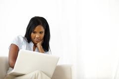 Calm young woman working on laptop at home. Natural portrait of a calm young woman working on laptop at home Royalty Free Stock Photography