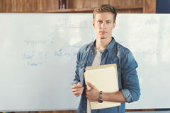 Calm youthful guy learning new information while training at work. Waist up portrait of serious young man standing with his back to flipchart and holding papers Royalty Free Stock Photography