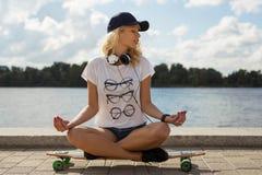 Calma de sensación de la muchacha mientras que se sienta en longboard Foto de archivo libre de regalías
