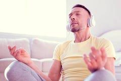 Calma do sentimento do homem e aliviado ao meditar e ao concentrar-se na música calma fotos de stock royalty free