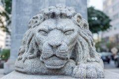 Calma squinning g di forza degli occhi della statua del leone dell'ambiente capo della città immagini stock