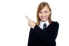 Calma y muchacha adolescente relajada que señalan de lado Imagen de archivo libre de regalías