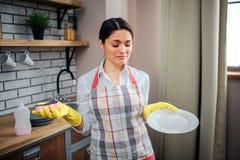 Calme gentil et support paisible de femme adulte dans la cuisine et pose sur la caméra Elle tiennent le plat blanc et l'éponge de photos libres de droits