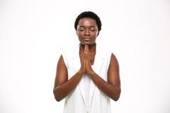 Calme a la mujer bastante africana con los ojos cerrados que se colocan y que meditan Foto de archivo